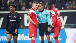 Referee Robert Hartmann (m.) im Austausch mit Oliver Fink (l.) und Dodi Lukebakio (r.)