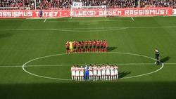 Die Spieler vom SC Freiburg und Fortuna Düsseldorf gedenken in einer Schweigeminute den Opfern der Gewalttat von Hanau