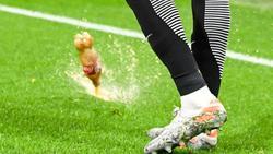 Eine fast voll Getränkeflasche landet neben dem Leipziger Christopher Nkunku im Groupama Stadion auf dem Spielfeld