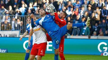 Regensburgs Torwart Philipp Pentke (r.) kommt vor Magdeburgs Doppeltorschütze Christian Beck (M.) an den Ball