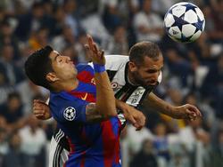 Chiellini kopt de bal weg in het duel met FC Barcelona-speler Luis Suárez