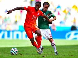 De Mexicaan Andrés Guardado (r.) probeert tevergeefs de bal van Georginio Wijnaldum (l.) te onderscheppen. (29-06-2014)
