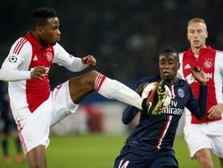 Ajax-verdediger Stefano Denswil (l.) gooit alles wat hij heeft in de strijd om de bal te veroveren bij PSG-middenvelder Blaise Matuidi (m.). Mike van der Hoorn (r.) kijkt naar het schouwspel. (25-11-2014)