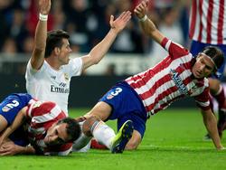 Reals Madrids Gareth Bale (M.) und Atléticos Diego (l.) Godin gehen nach einem Zweikampf zu Boden