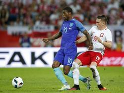 Georginio Wijnaldum (izq.) recibe la presión por la espalda de Piotr Zieliński. (Foto: Getty)