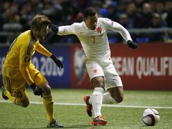 Memphis Depay (r.) houdt tijdens Kazachstan - Nederland de enige speler van Kazachstan met ervaring in een grote Europese competitie van zich af. Konstantin Engel speelt zijn wedstrijden in de Duitse Bundesliga. (10-10-2015)