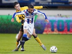 Hicham Faik (l.) probeert tijdens de Eredivisie-wedstrijd tussen sc Heerenveen en Roda JC Caner Çavlan (r.) af te stoppen, maar daar slaagt de middenvelder niet in. (28-11-2015)