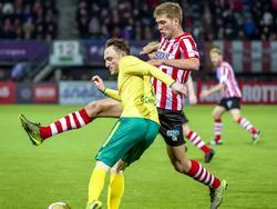 Joeri Schroyen (l.) wil de bal wegwerken, maar de lange Roland Bergkamp steekt daar letterlijk en figuurlijk een stokje voor. (18-03-2016)