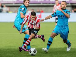 Loris Brogno (m.) versnelt met de bal aan de voet langs Guus Til (l.) en Illias Bel Hassani van AZ. (02-10-2016)