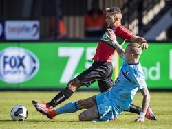 Rick Karsdorp (r.) glijdt Mohamed Rayhi (l.) van de bal tijdens NEC Nijmegen - Feyenoord.
