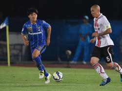 Ritsu Doan (l.), de aanvaller van Gamba Osaka, maakt zijn debuut voor de Japanse ploeg. Rechts dribbelt Cha Du Ri op met de bal. (27-05-2015)