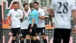 Die FCA-Profis diskutieren mit Schiedsrichter Tobias Welz über eine Elfmeterszene