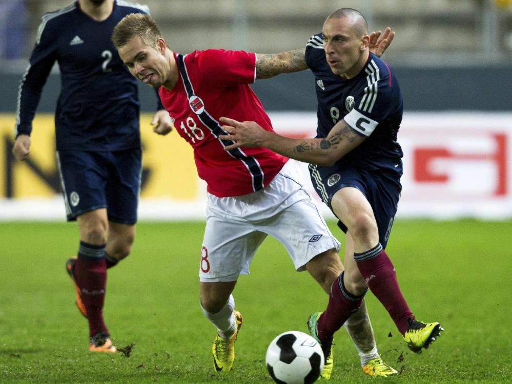 Marcus Pedersen (links) trifft mit Fußfessel am Bein
